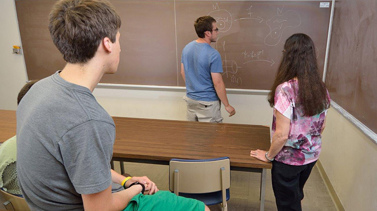 Four math majors face the front of a classroom and examine an advanced mathematics equation written on the chalkboard.