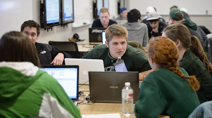Groups of applied engineering students — many of them wearing Spartan gear — sit at study tables, deep in conversation.