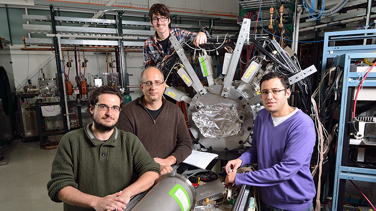 Students pursuing an astrophysics degree and a professor pose in front of equipment used for astrophysics.