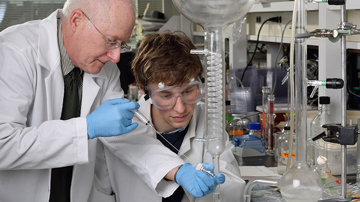 A professor shows a biochemistry major wearing goggles how to use laboratory equipment.