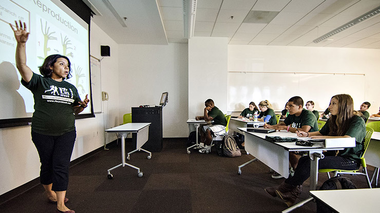 A professor instructs a classroom of biological sciences majors wearing Spartan-green shirts and listening attentively.