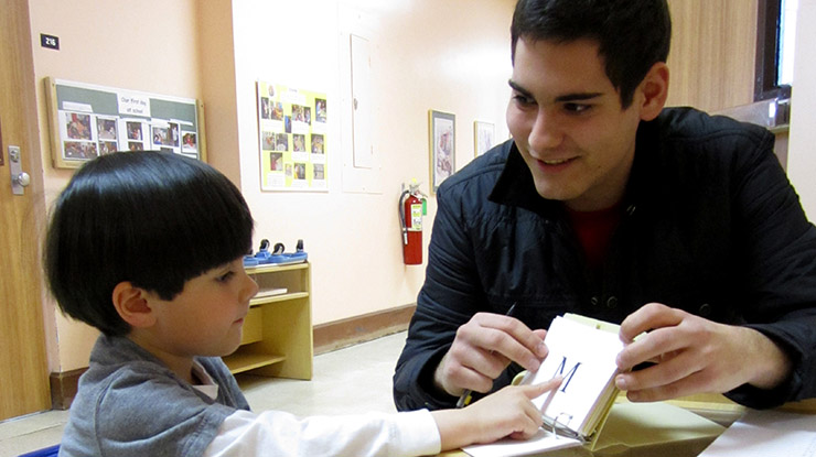A student pursuing a child development degree sits with a young child who points to the letter 'M' on a teaching card.