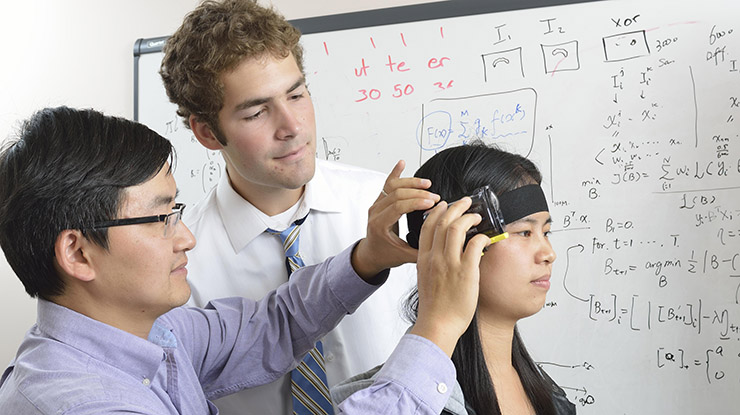 A professor affixes a computer science device around the head of a student pursuing a computer science degree.