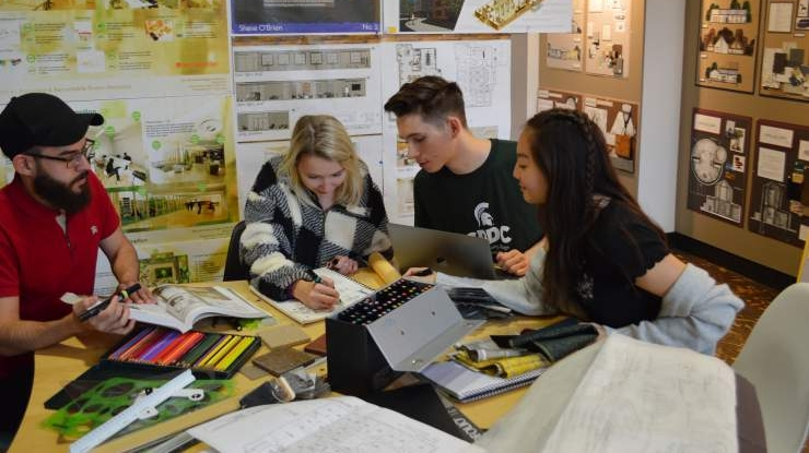 Students working toward an interior design degree sit at a table surrounded by colorful interior design materials.