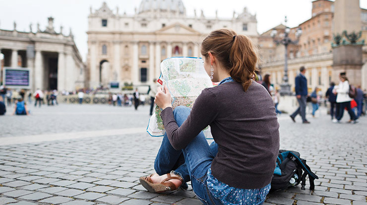 A religious studies major sits on the ground and looks at a map while on education abroad.
