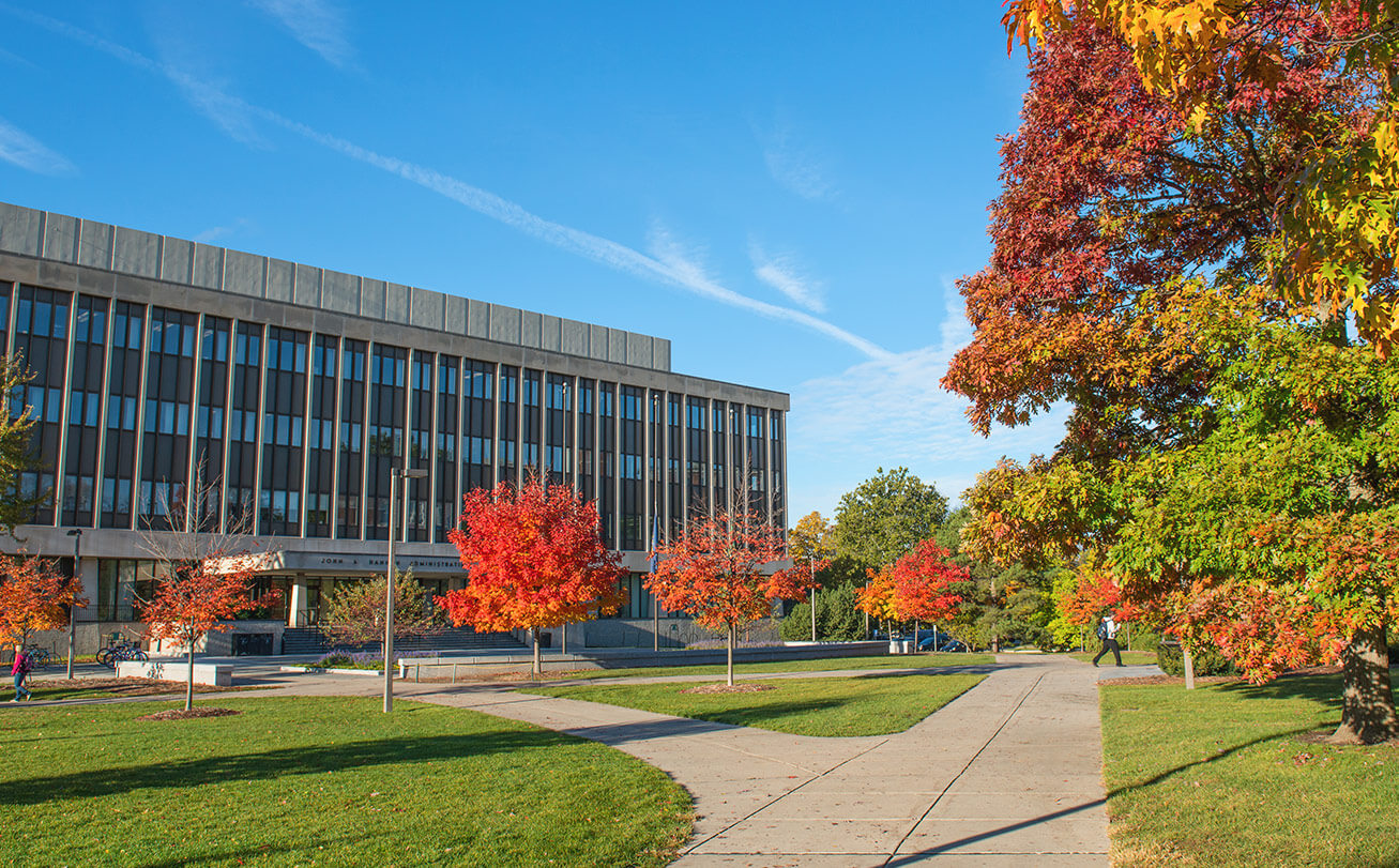 The Hannah Administration building on a sunny day surrounded by trees with red and green leaves.