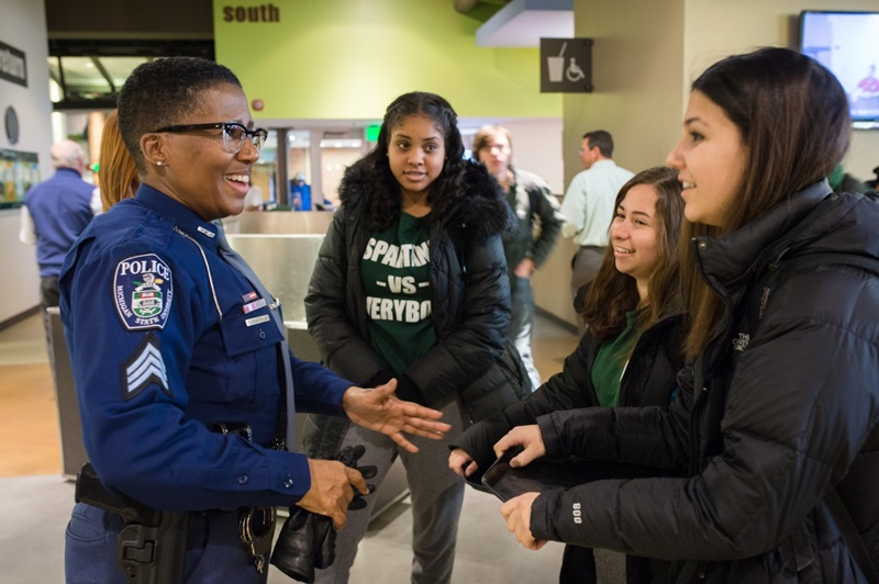 An MSU police officer engaged in a friendly conversation with a group of students.