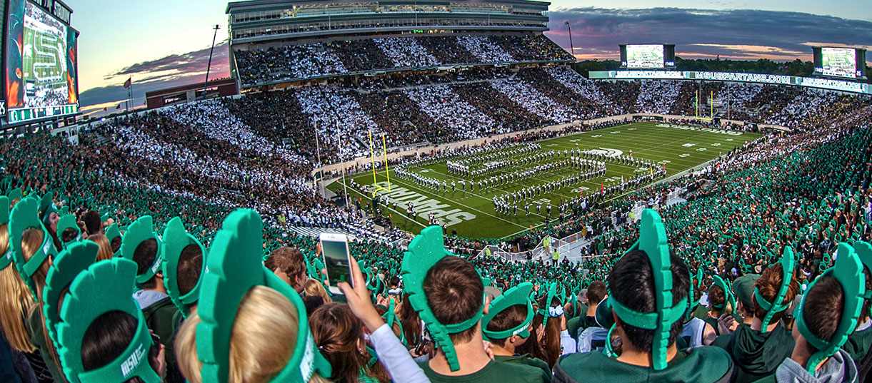 Students at Michigan State University's Spartan Stadium cheer on the football team.