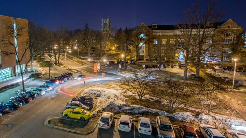 An aerial time lapse of cars driving past a parking lot on MSU's campus at night